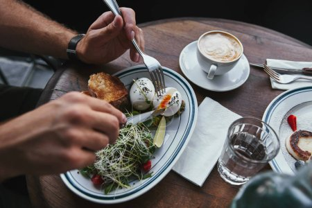 cropped shot of man eating salad with sprouts and eggs at restaurant