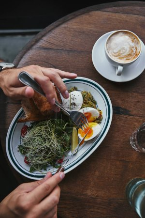 Photo for Cropped shot of man eating healthy salad with sprouts and cup of coffee at restaurant - Royalty Free Image