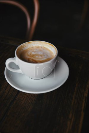 close-up shot of cup of delicious coffee on rustic wooden table at restaurant