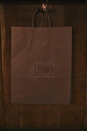 blank paper bag hanging on wooden wall