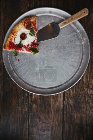 top view of slice of pizza with server on metal tray and wooden table