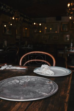 empty metal kitchen tray with white plate on wooden table at restaurant
