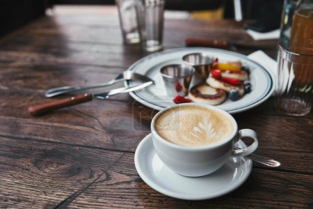 close-up shot of curd pancakes on plate and cup of coffee on rustic wooden table