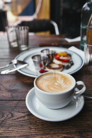Photo for Close-up shot of delicious syrniki on plate and cup of coffee on rustic wooden table - Royalty Free Image