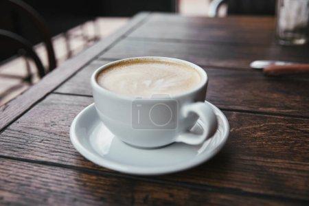 Photo pour Plan rapproché de tasse de café sur une table en bois rustique au restaurant - image libre de droit