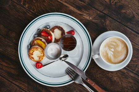 top view of delicious syrniki on plate and cup of coffee on rustic wooden table