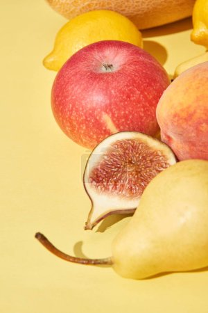close-up view of fresh ripe pear, apple, peach, fig and lemons on yellow