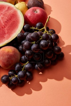 top view of fresh ripe sweet grapes, peach, apple and watermelon on red