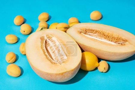 Photo pour Vue rapprochée du melon et des citrons mûrs coupés en deux avec des abricots sur fond bleu - image libre de droit