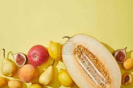 top view of halved melon and fresh ripe fruits on yellow background