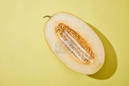 top view of fresh ripe halved melon on yellow background