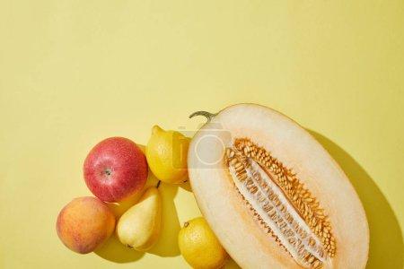 Photo pour Vue de dessus du melon, de la pomme, de la pêche, de la poire et des citrons coupés en deux sur fond jaune - image libre de droit