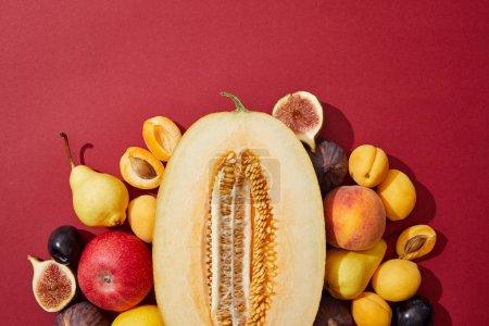 Photo pour Vue de dessus de divers fruits frais sucrés mûrs sur fond rouge - image libre de droit