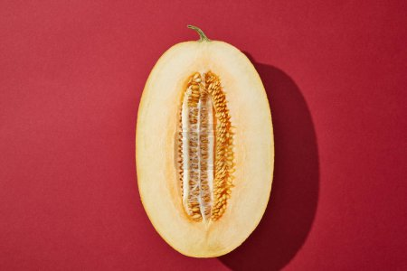 top view of halved fresh ripe tasty melon on red background