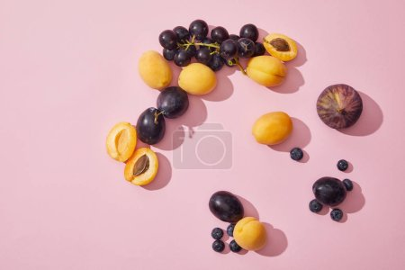 top view of fresh ripe sweet apricots, grapes, plums, blueberries and fig on purple background