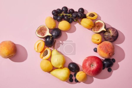 top view of fresh ripe sweet tasty fruits on purple background