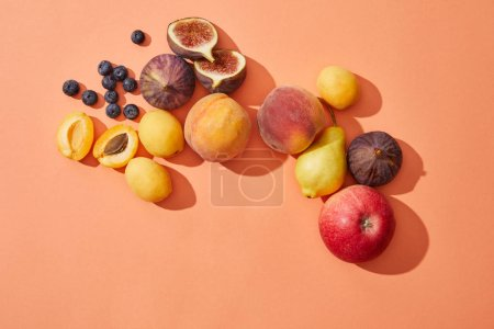 Photo for Top view of fresh ripe sweet tasty fruits on red background - Royalty Free Image