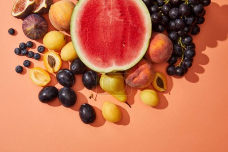 Photo for Top view of various fresh ripe sweet summer fruits on red - Royalty Free Image