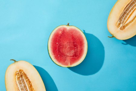 top view of fresh ripe sweet halved melon and watermelon on blue