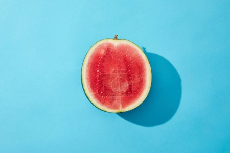 Photo for Top view of fresh ripe sweet halved watermelon on blue - Royalty Free Image