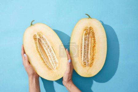 cropped shot of female hands and halved ripe melon on blue