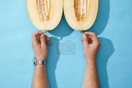 Photo pour Plan recadré de mains humaines et de melon mûr coupé en deux sur bleu - image libre de droit