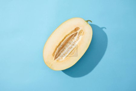 top view of half of fresh ripe sweet melon on blue background