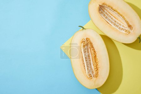 top view of halved ripe melon on blue and yellow background