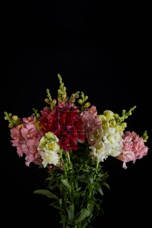 bouquet of beautiful fresh flowers with buds isolated on black background