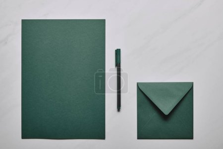 Green letter template with envelope and pen on white marble background