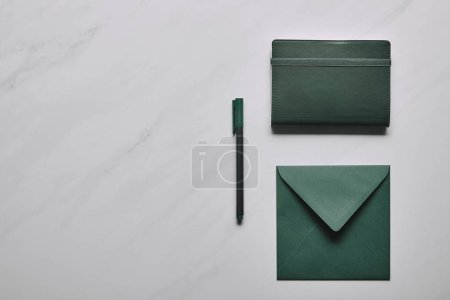 Green envelope and notebook with pen on white marble background