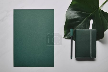 Photo for Green stationery set and monstera leaf on white marble background - Royalty Free Image