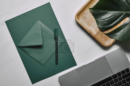 Green paper for letter template by laptop on white marble background