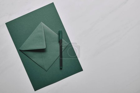 Green envelope with pen on white marble background