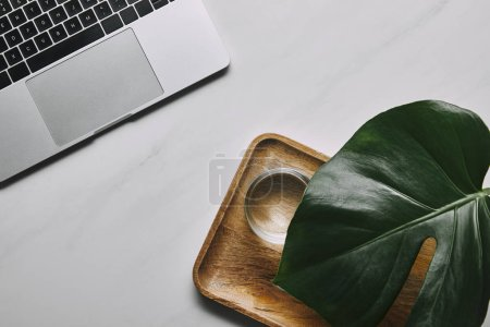Laptop by wooden tray with water and monstera leaf on white marble background