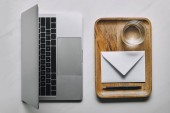 Workplace template with laptop and wooden tray with envelope and water on white marble background
