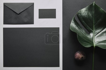 Business mock up with black envelope and card on white marble background
