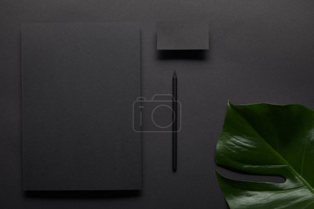 flat lay with Business mock up with black notebook and card on black background