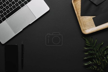 Smartphone and laptop on black background with wooden tray and green leaf