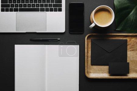 Photo pour Carnet ouvert et papeterie par ordinateur portable sur fond noir - image libre de droit