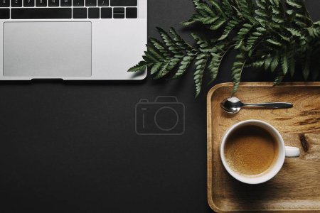 Cup of black coffee by laptop on black background