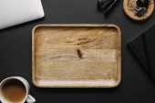 Empty wooden board on black background with laptop and stationery