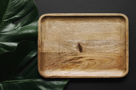 Empty wooden board on black background with monstera leaves