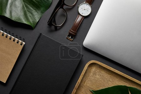 flat lay with Notebook and laptop with glasses and watch on black background