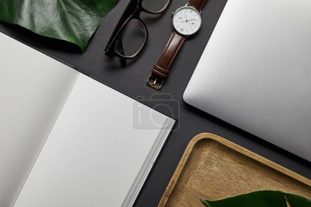 Flat lay template with open notebook and laptop on black background