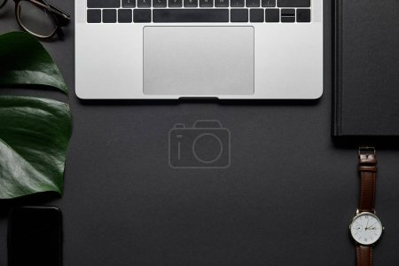 Composition with laptop and business accessories on black background