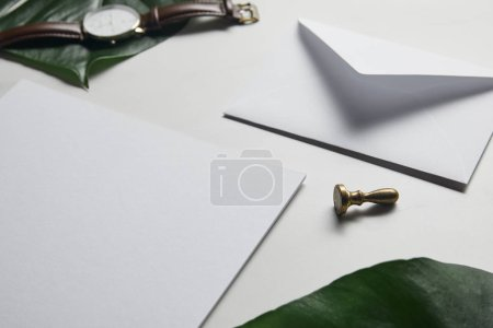 Business template with paper, envelope and watch on white marble background