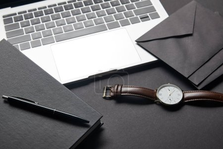 Laptop with black envelope and watch on black background