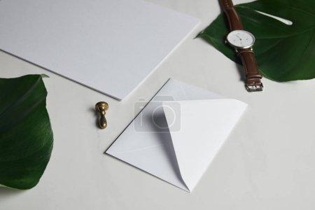 Photo pour Enveloppe vierge et montre sur fond de marbre blanc avec des feuilles vertes - image libre de droit
