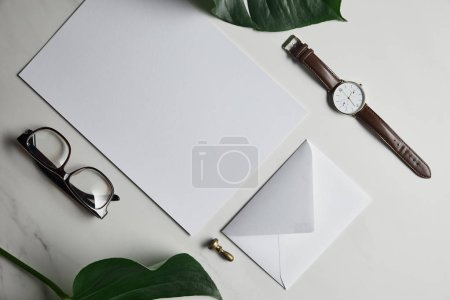 Stationery template with watch and glasses on white marble background with monstera leaves